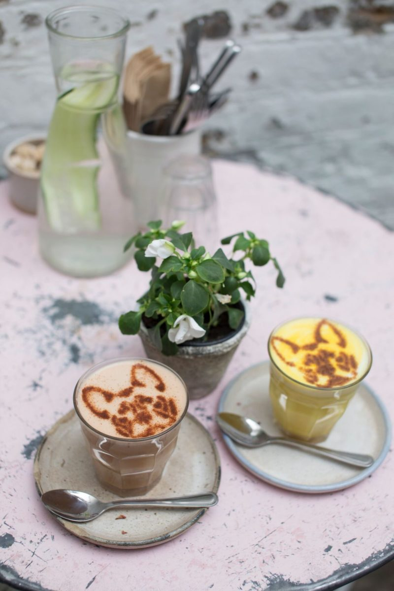 Quirky coffee drinks on a pink table and two glasses.