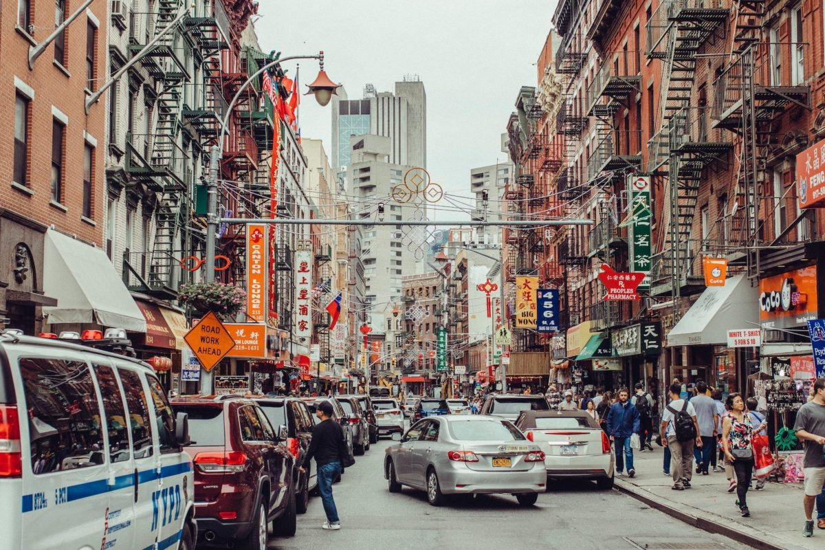 cars and people passing through new york city's busy chinatown neighborhood