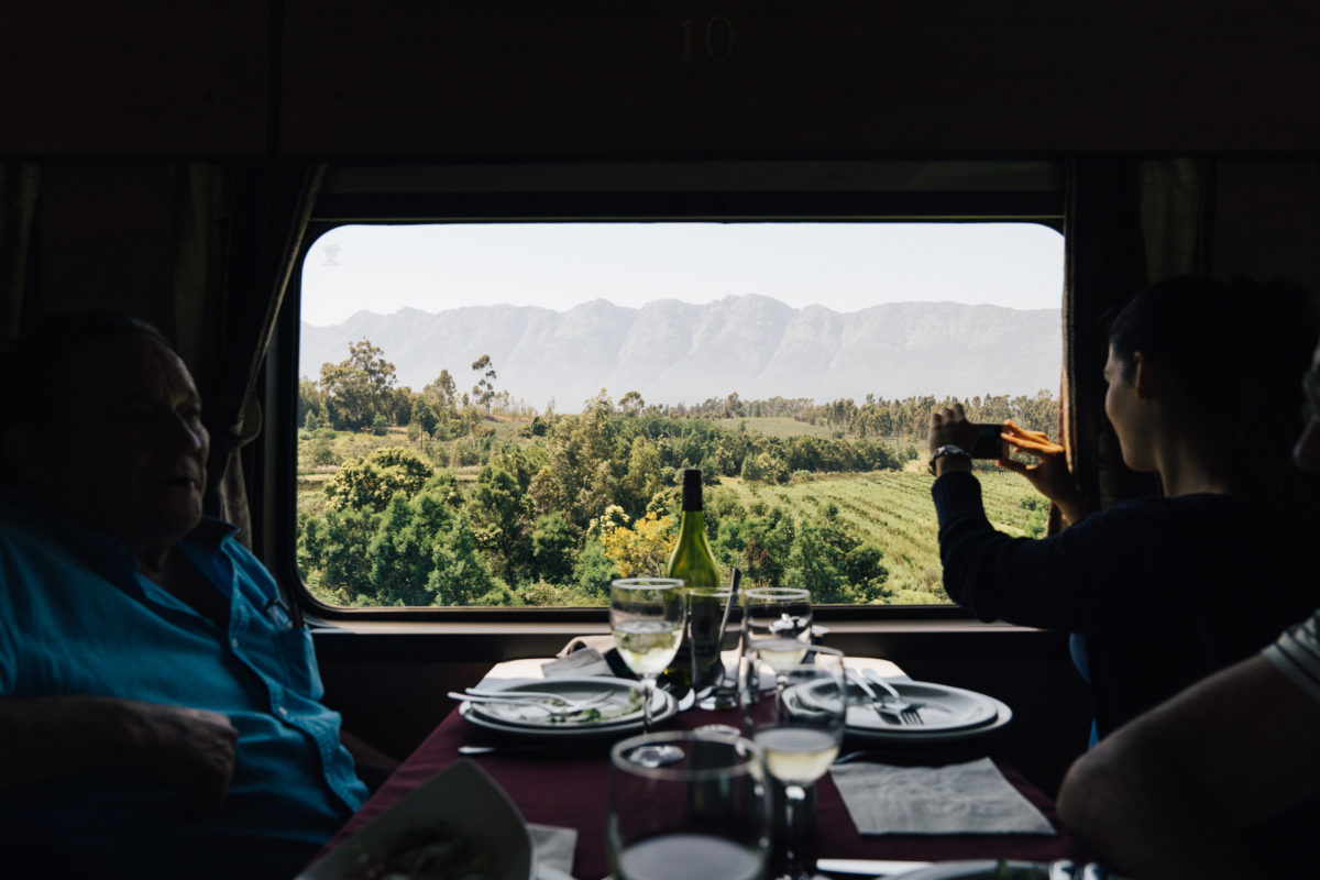 couple in a train's dining car taking photos of the scenery outside