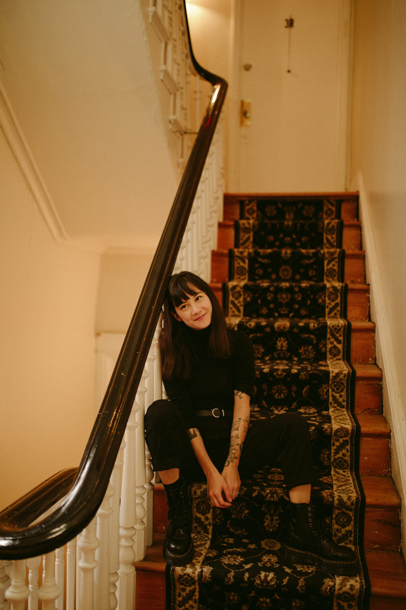 a girl sits at the bottom of a flight of stairs