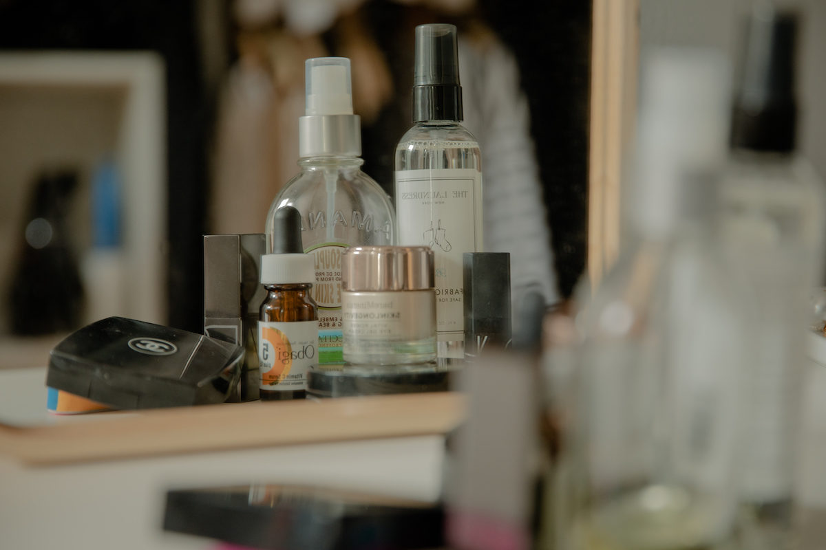 beauty products on a vanity counter reflected in a mirror