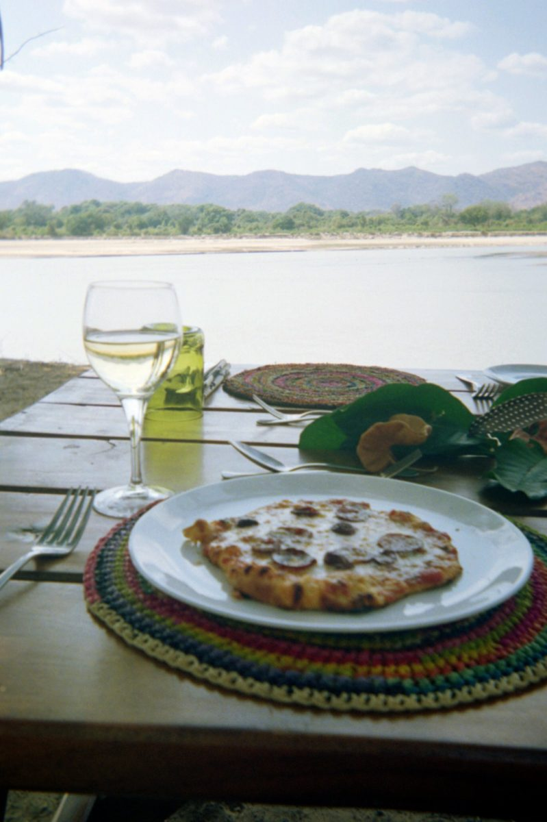 A personal pizza with glass of white wine overlooking a river in zambia's south luangwa national park