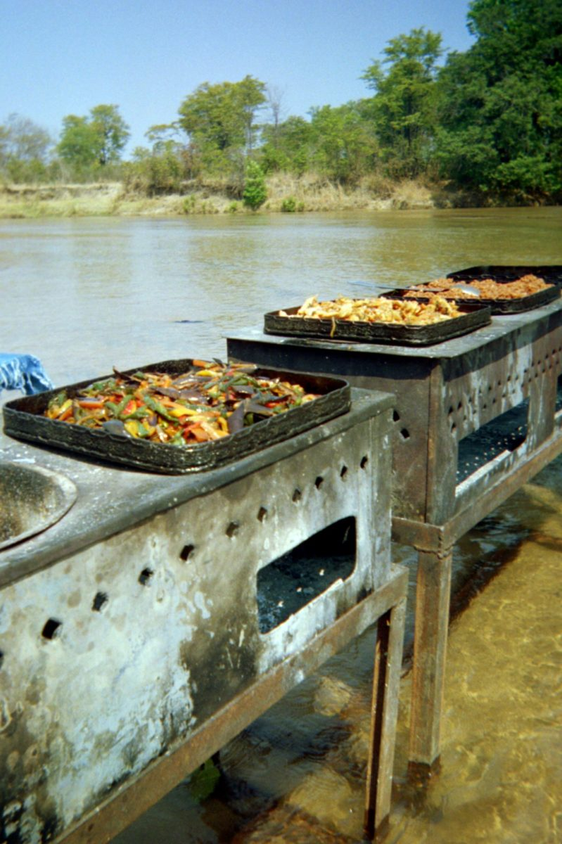 mobile stoves in the river cooking various meats and peppers in zambia's south luangwa national park
