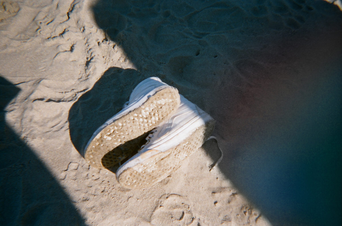 a pair of white sneakers in the sand