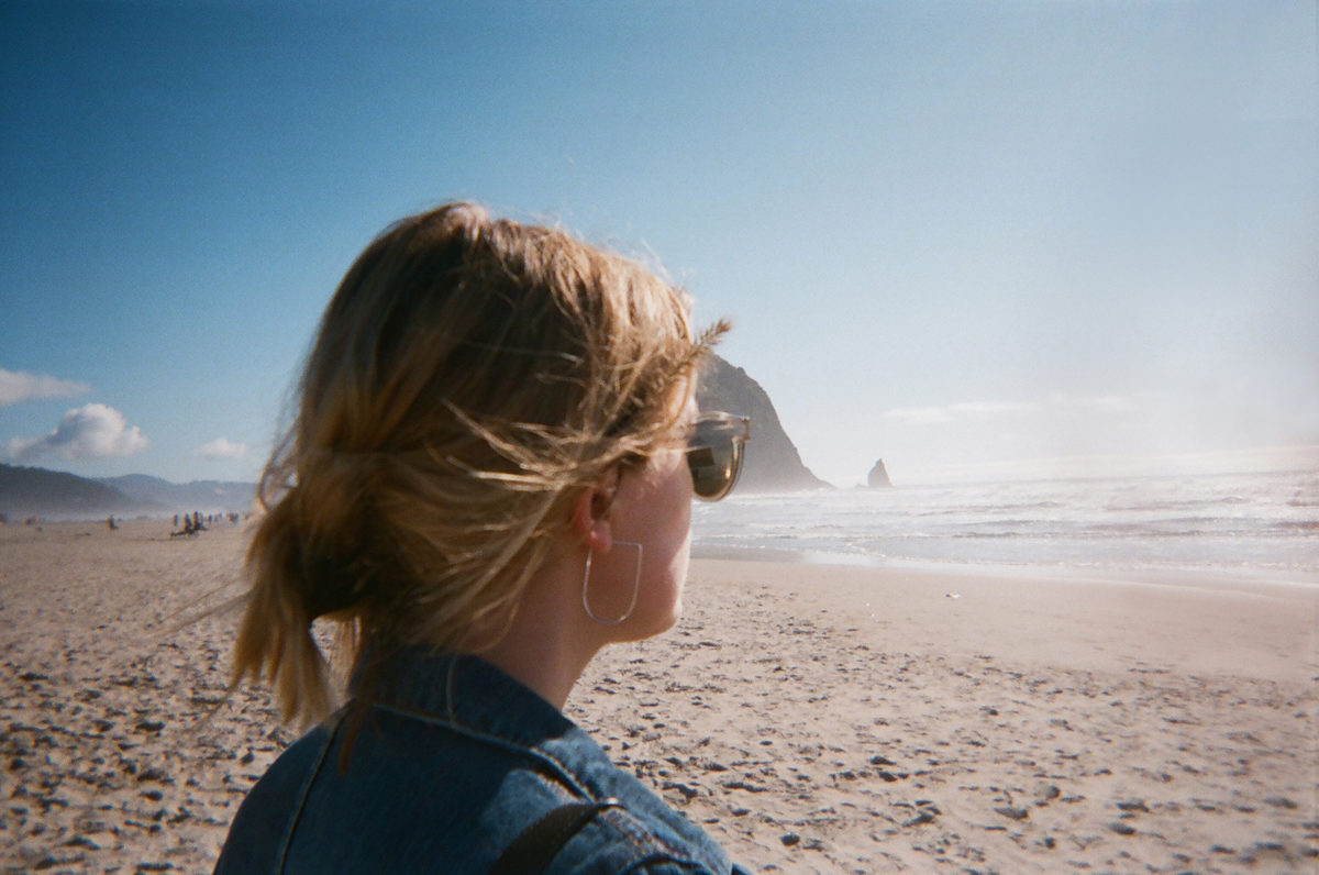 blonde woman stands on the beach in Oregon in front of haystack rock