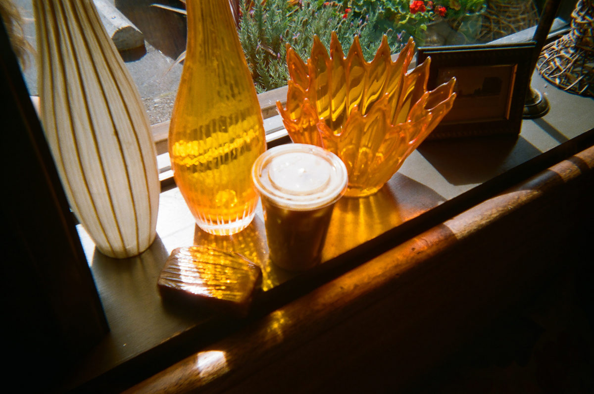 iced coffee, banana bead, and kitschy glassware on a windowsill with sunlight pouring through