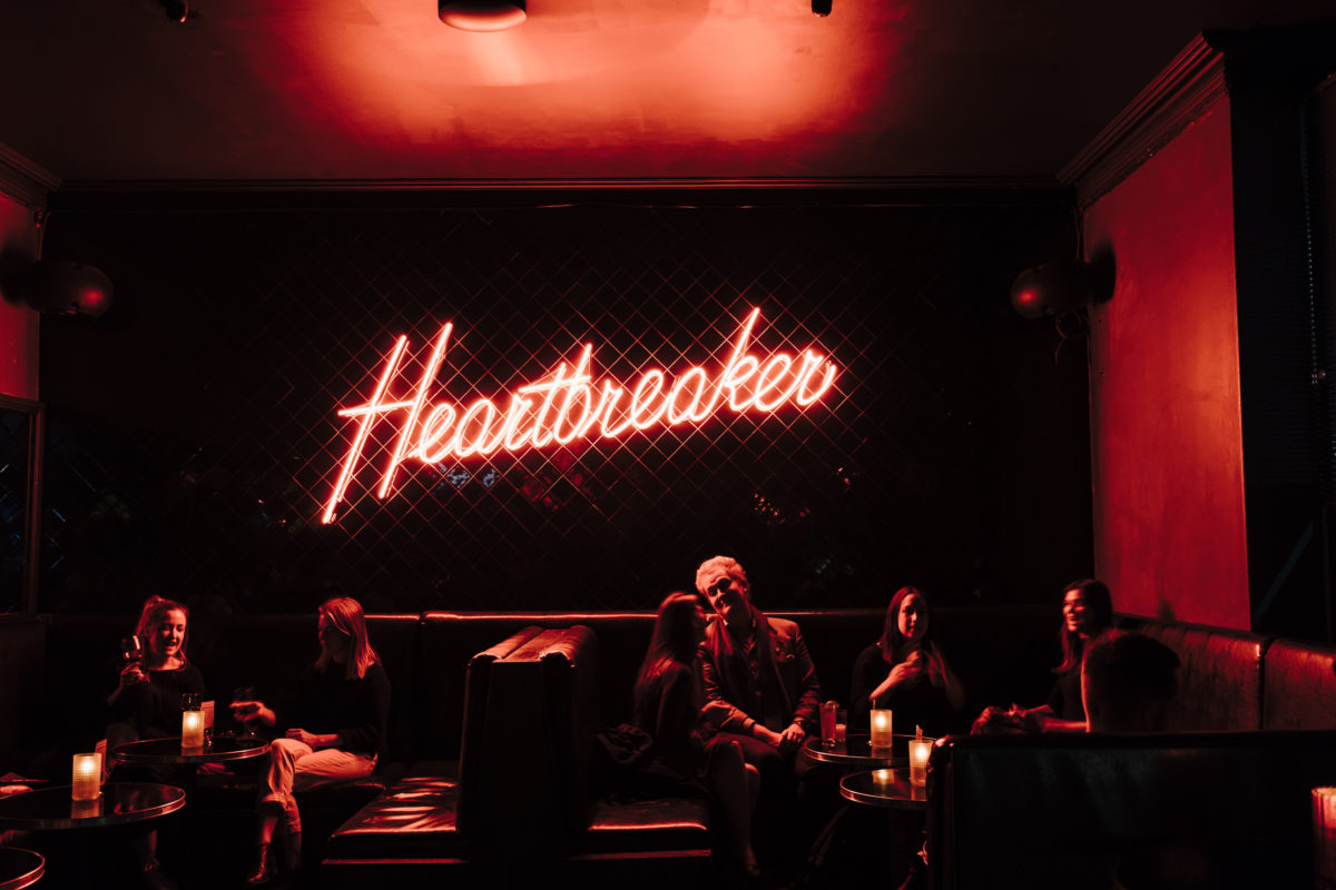 "A neon sign reading ""Heartbreaker"" inside a dark bar."