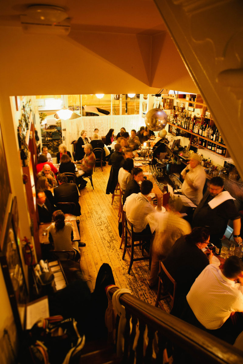 A crowd of people inside a golden-lit bar.