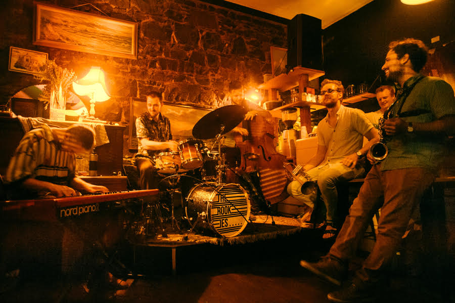 A group of rock musicians plays on a small stage inside a golden-lit bar.