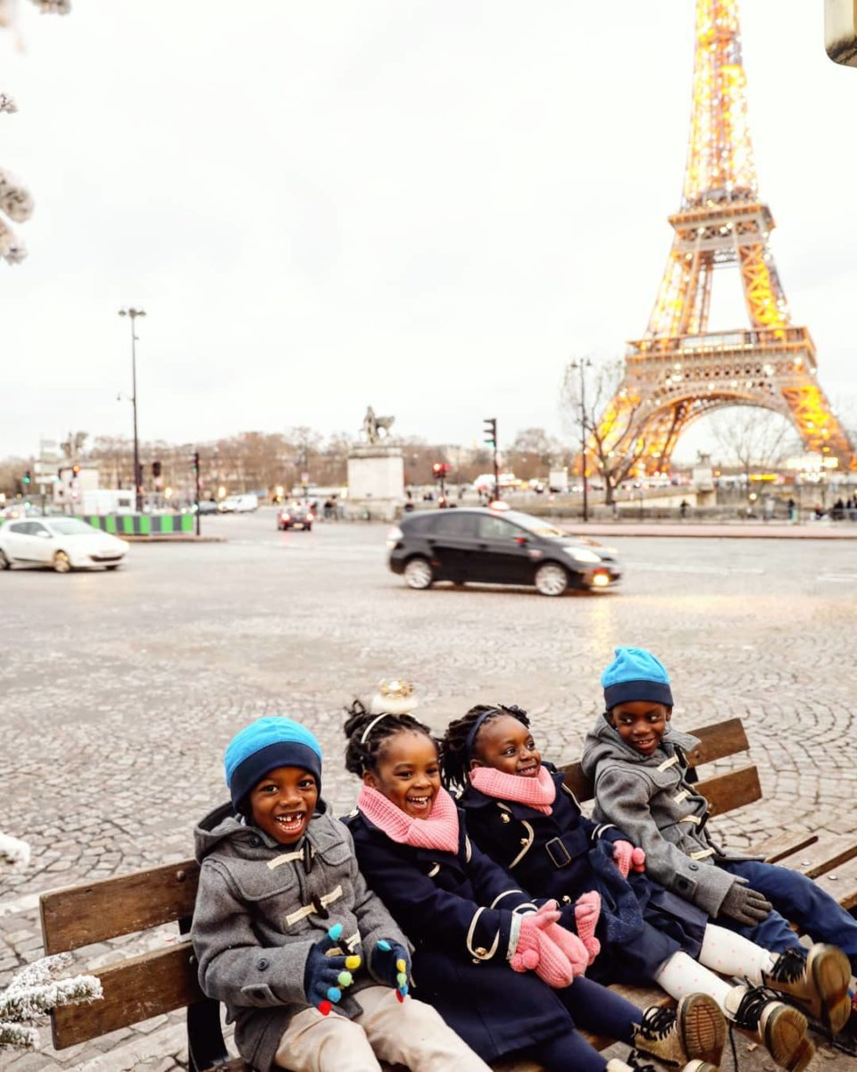 Four kids smile on a bench in front of the eiffel tower