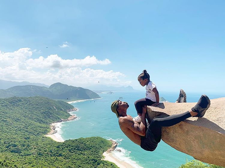 With a beautiful beach and jungle in the background, a father leans up from a cliff to give his daughter a kiss