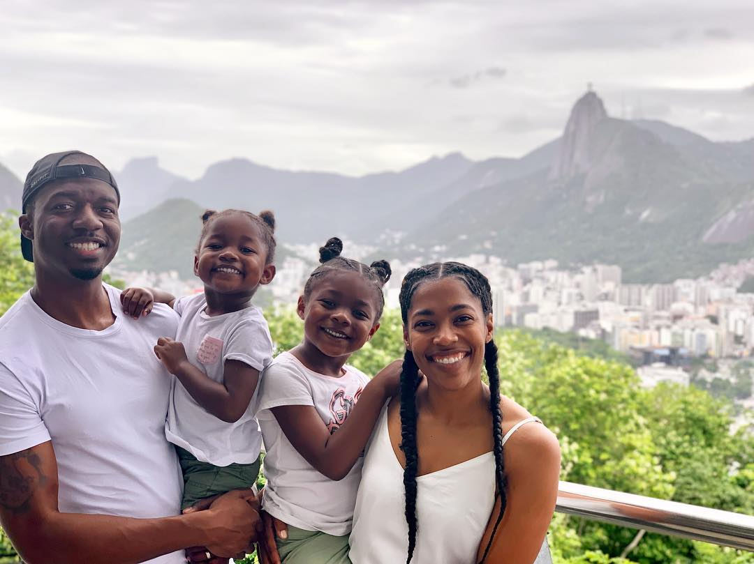 A family dressed in all white smiles with the mountains and city of Rio de Janeiro in the background.