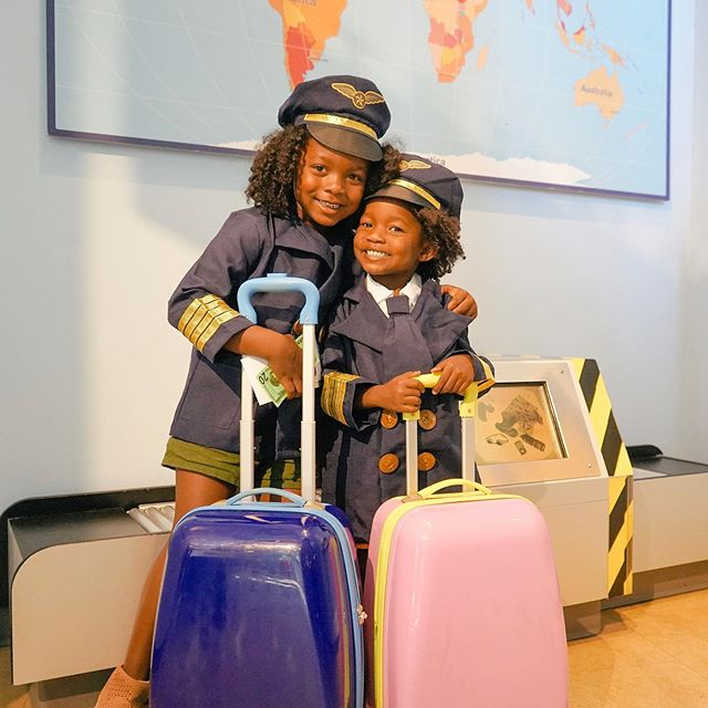 Two children wearing pilot costumes hold suitcases in front of a world map.