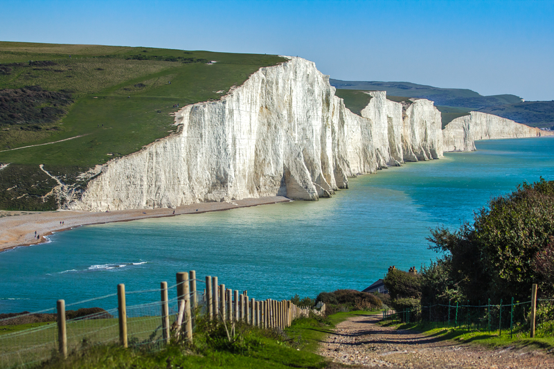 White cliffs topped with green grass dance along the side of a turquoise-blue ocean