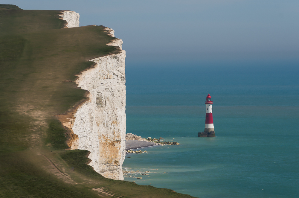 White cliffs topped with green grass overlook a turquoise blue ocean and a red and white lighthouse.