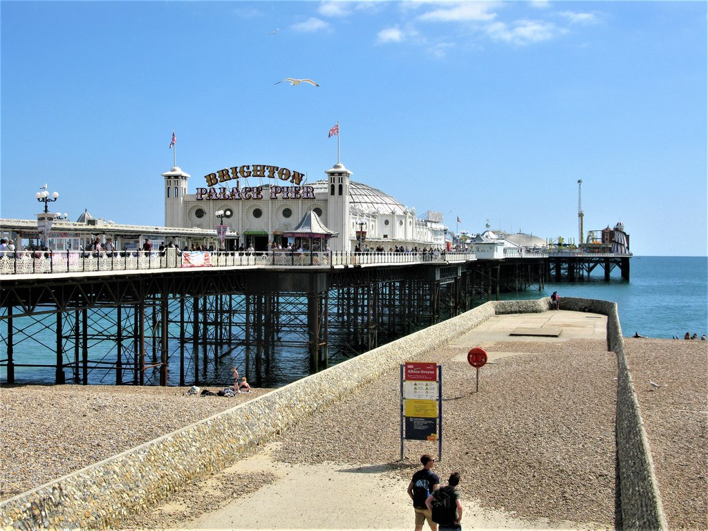 "A long pier above a blue ocean leads up to a large white building with a colorful sign reading ""Brighton Pier"""