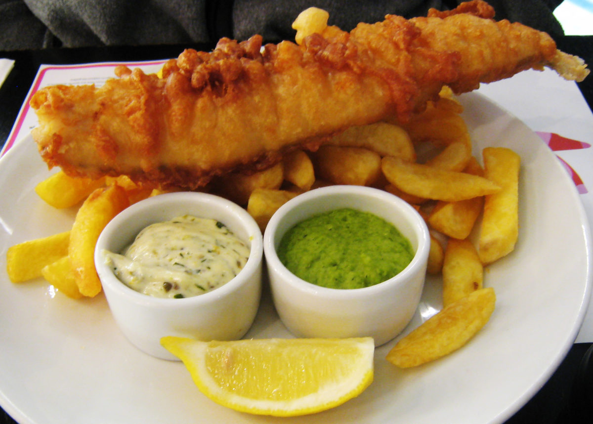 Fish, chips, mushy peas, tartar sauce, and lemon on a white plate