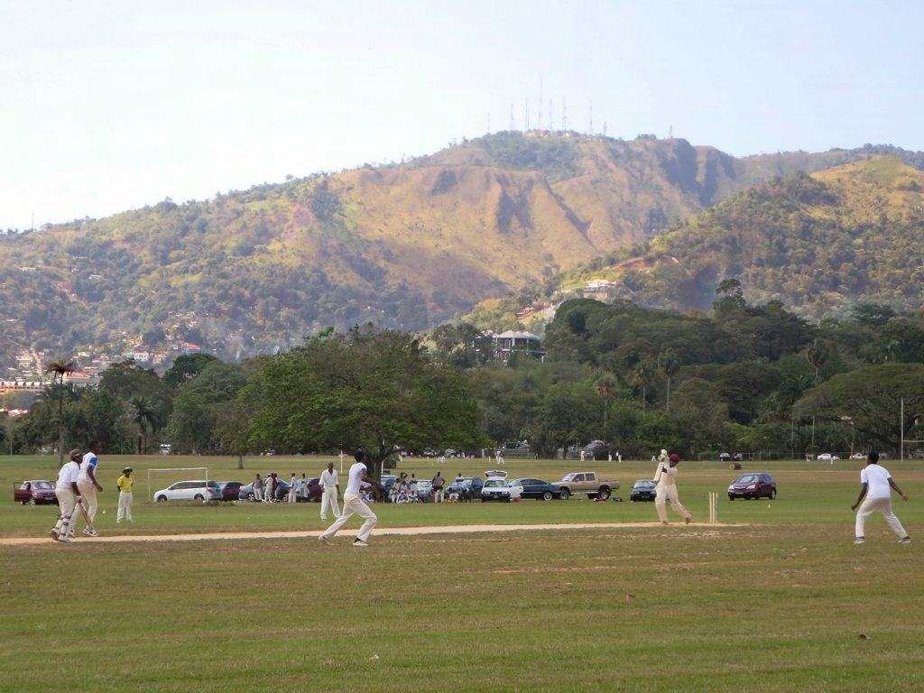 People play soccer on a green lawn with a large mountain in the distance
