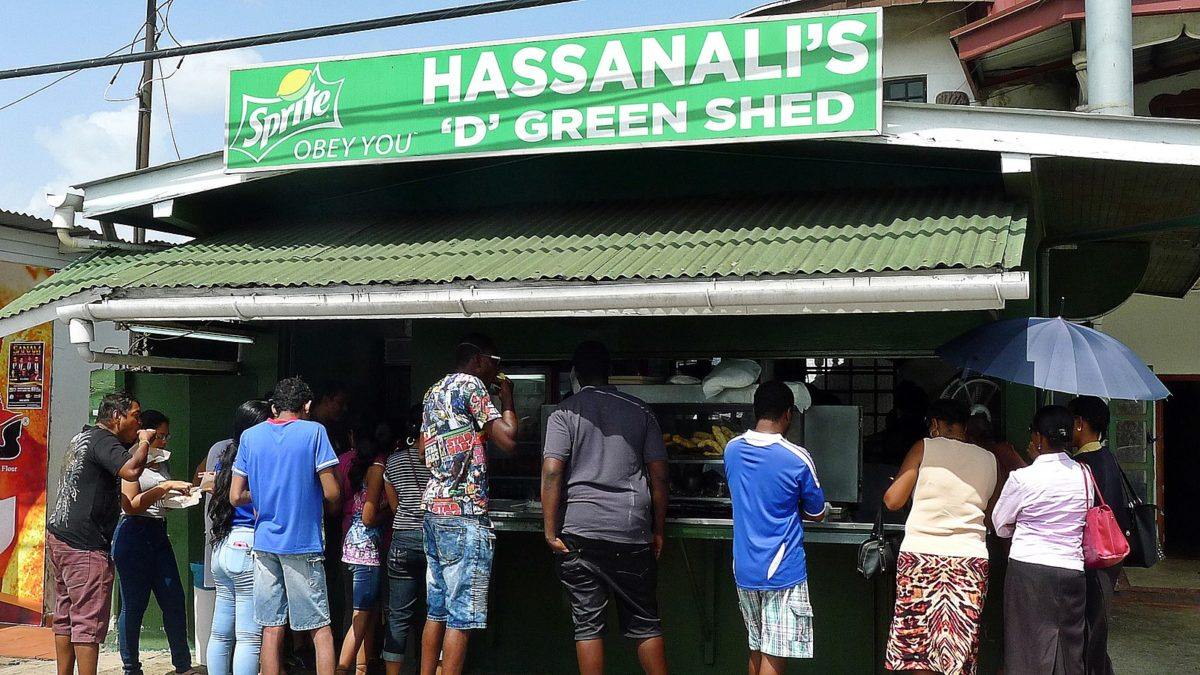 "People gathered in front of a green food stand with a large sign reading ""Hassanali's"""