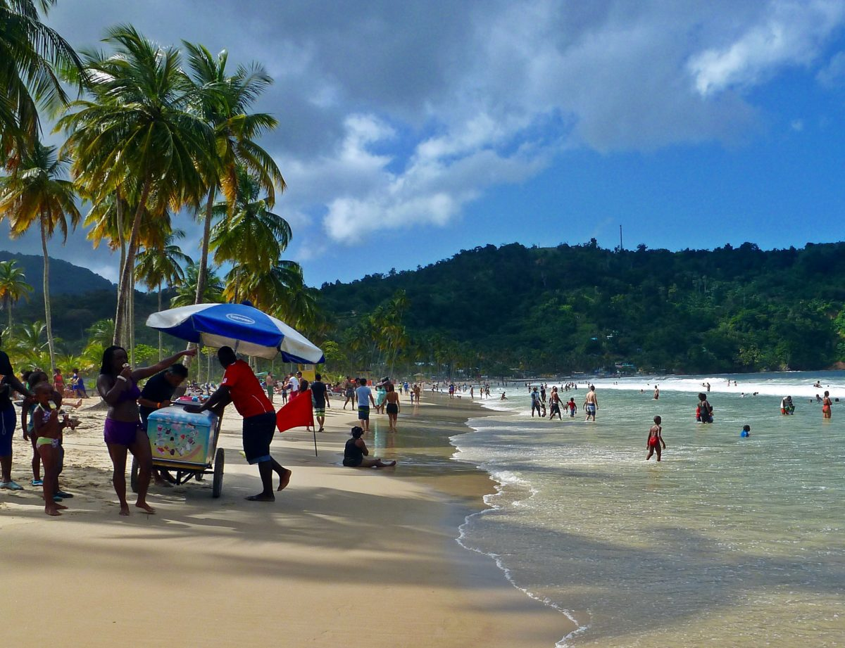 A tropical beach filled with people and a lush green mountai