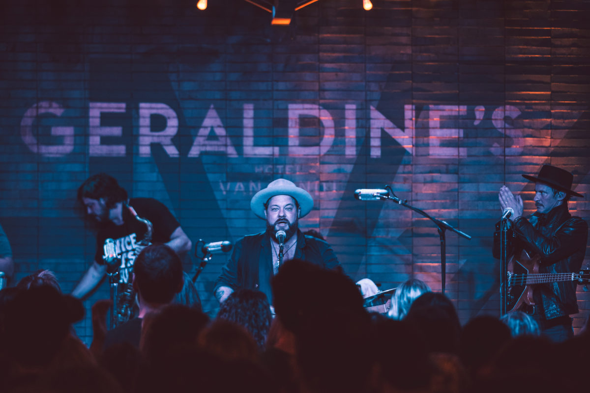 "A singer illuminated in blue performs onstage for a crowd in front of a brick wall painted with the phrase ""Geraldine's"""