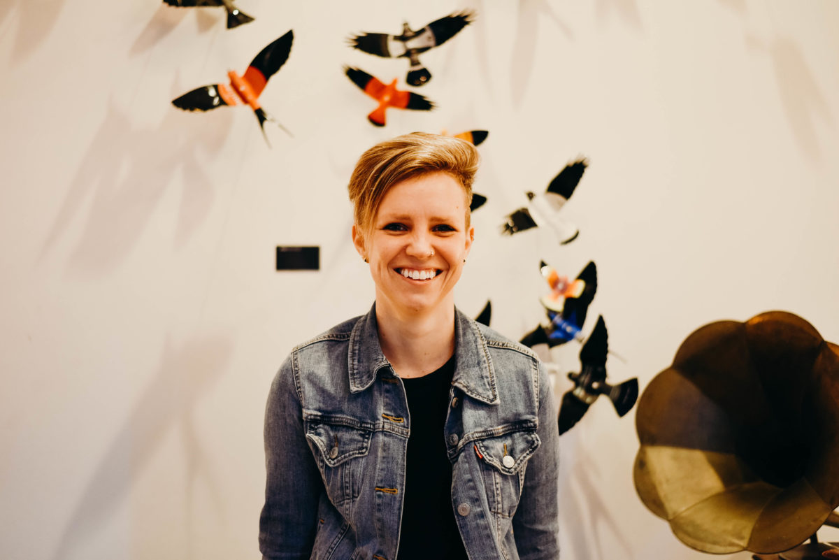 A woman with short blonde hair in a black shirt and denim jacket smiles in front of a white wall decorated with birds