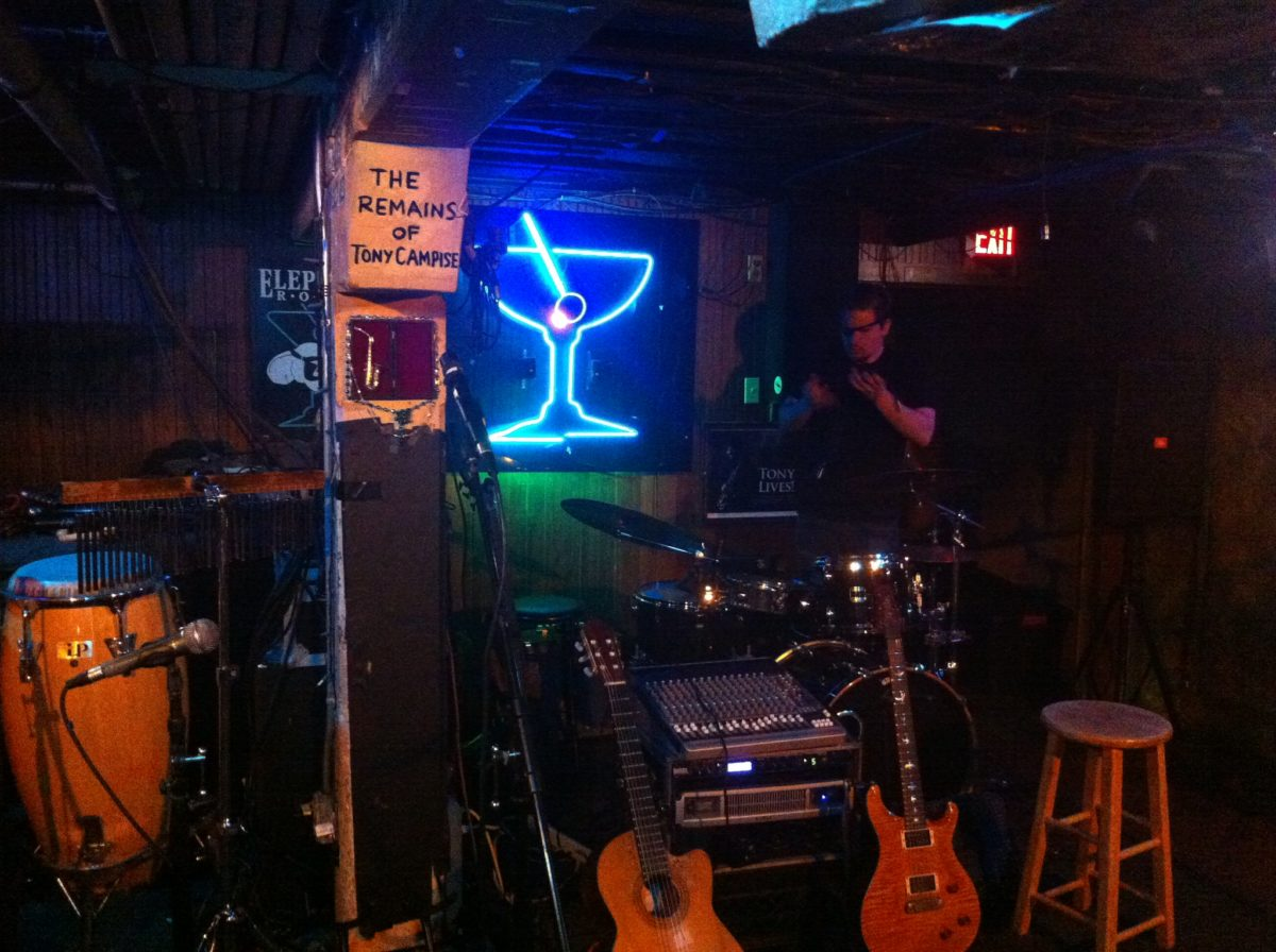 two red guitars sit beneath a neon sign resembling a martini glass inside a dark music venue
