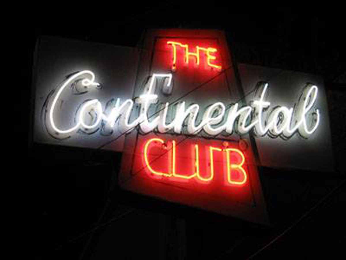 "a red and white neon sign reading ""The Continental Club"""