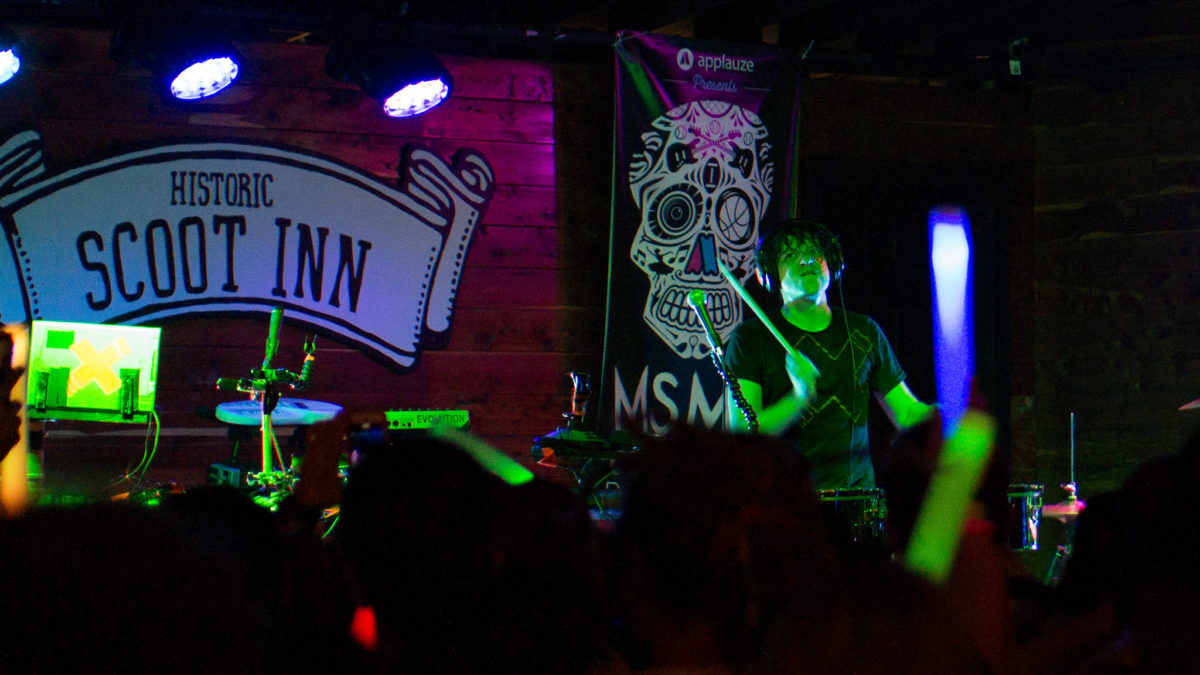 "A performer with black hair and illuminated by green light performs for a dark crowd in front of a painted sign resembling a scroll that reads ""Historic Scoot Inn"""