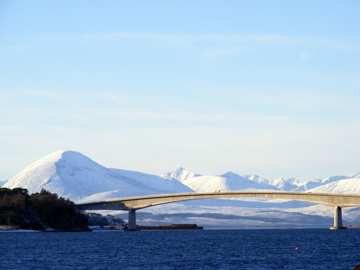 A thin bridge in front of a series of snowy mountains at dawn