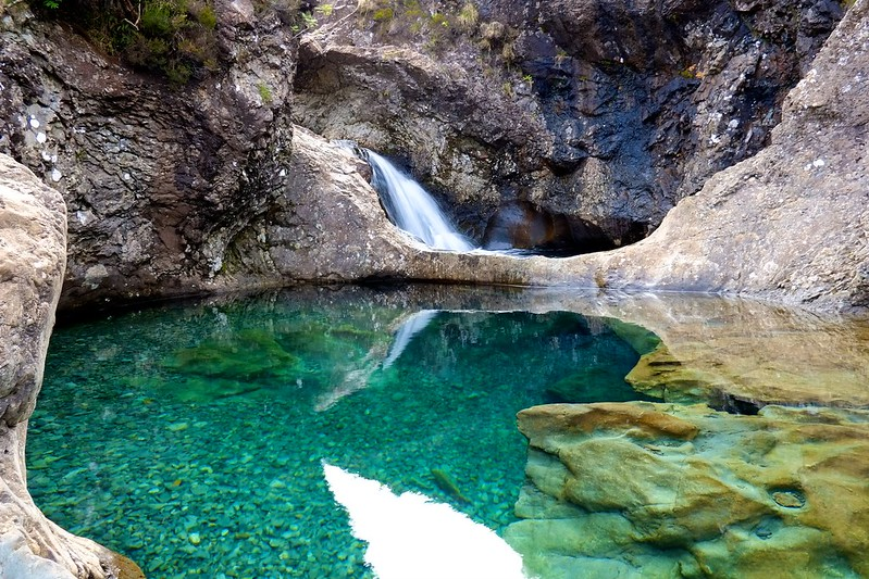 A small waterfall fills a rocky cavern with vibrant turquoise water