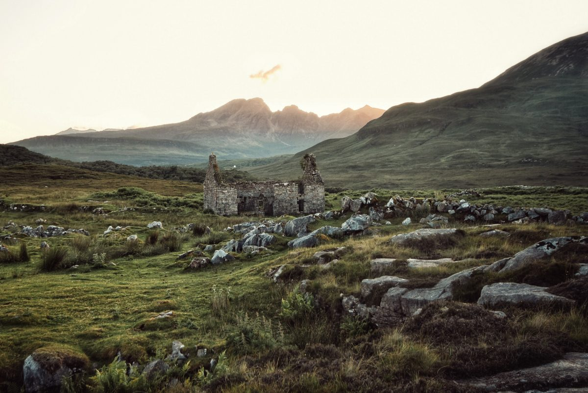 the ruins of a castle sit in the middle of a rocky green field at dawn