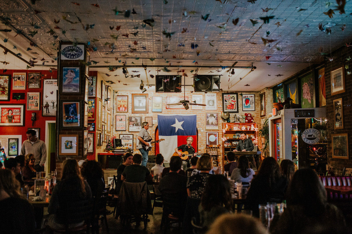 A crowd sits before a stage on which a man plays guitar with the Texas flag hung on the colorful behind him