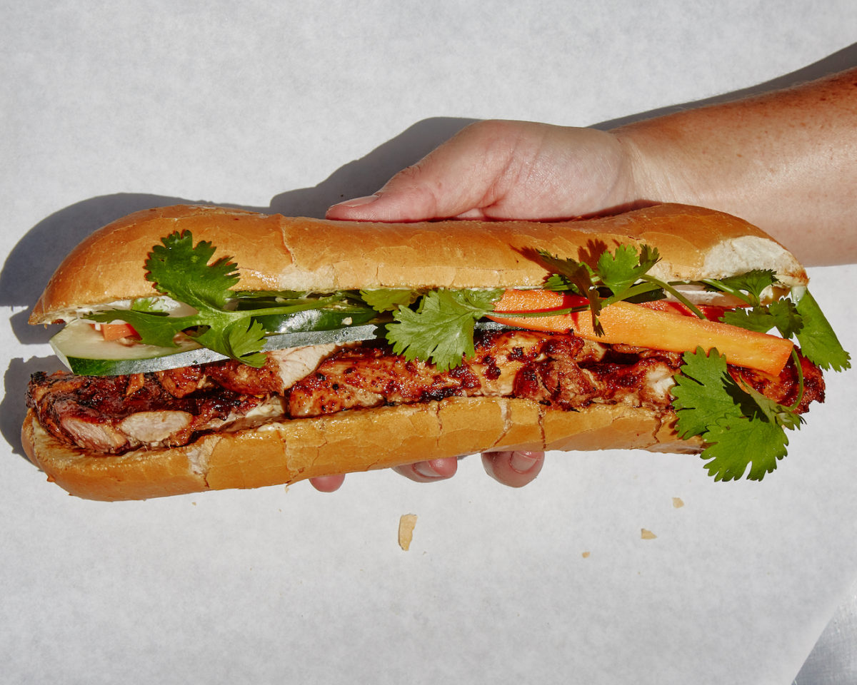 a hand holds a bánh mì sandwich filled with meat and greens