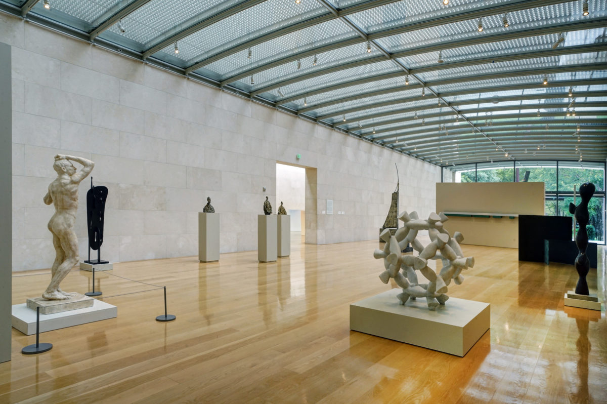 a large white room with light wood floors and a glass ceilling containing several modern sculptures
