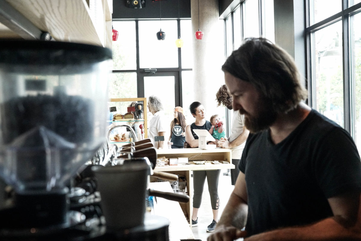 A dark foreground in which a bearded man prepares coffee and a light background in which groups of people sit in front of a bright window