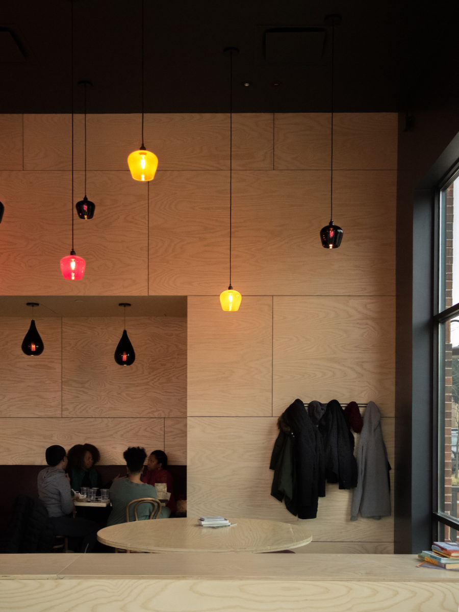 lights hang down in front of a light wood wall, beneath which sits a long row of black and gray coats to the right and a group of friends sitting to the left