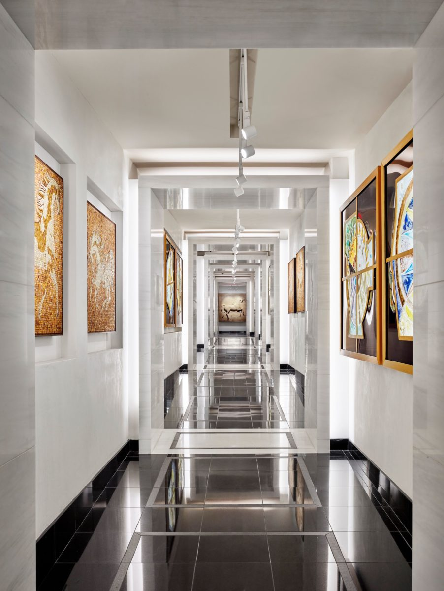 A long, white, brightly lit hallway with paintings in gold frames running along the walls