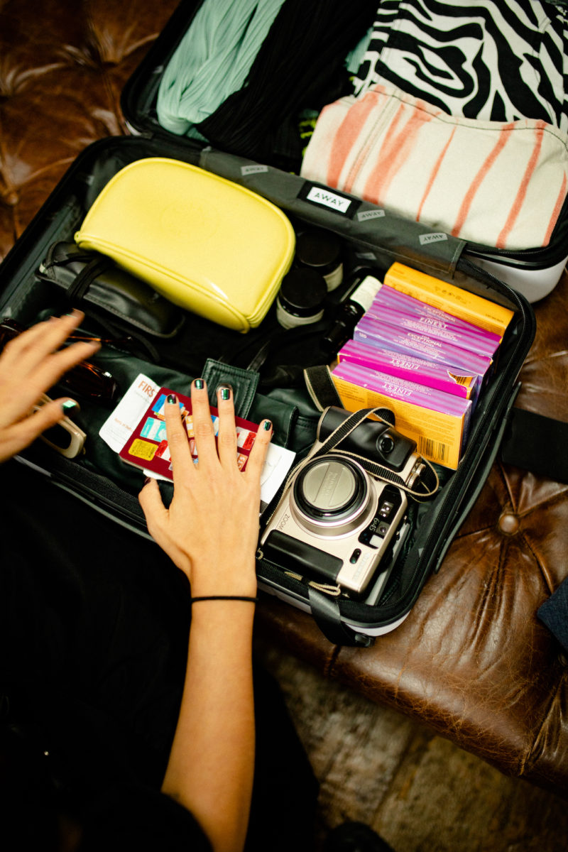 hands pack a bag filled with a camera, a makeup bag, boxes of film, and clothes