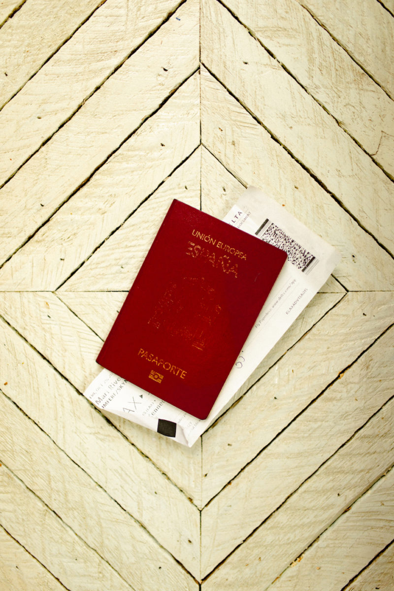 a red Spanish passport sits in the middle of a white, diamond-shaped wood panel