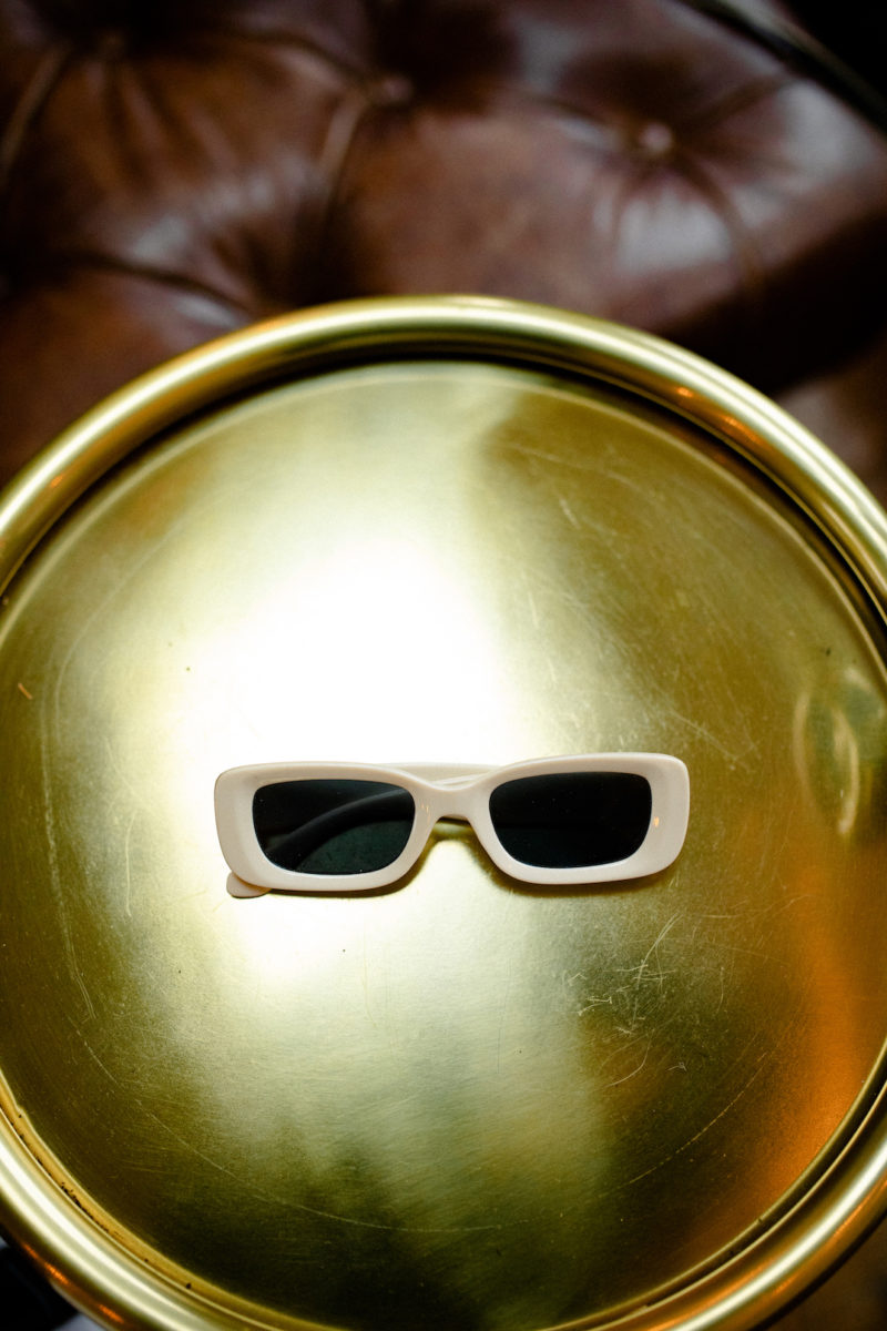 a pair of white sunglasses sit on top of the gold plate