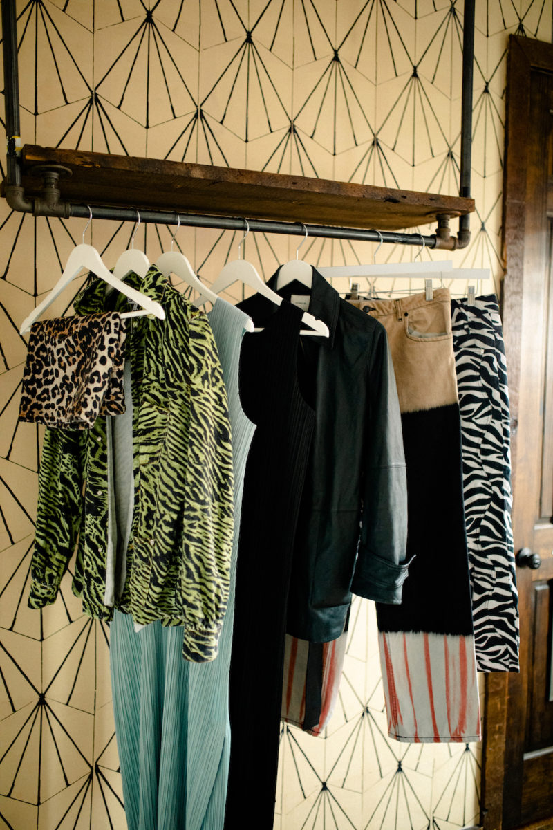 a rack of colorful and eclectic patterned clothes hang from a rack