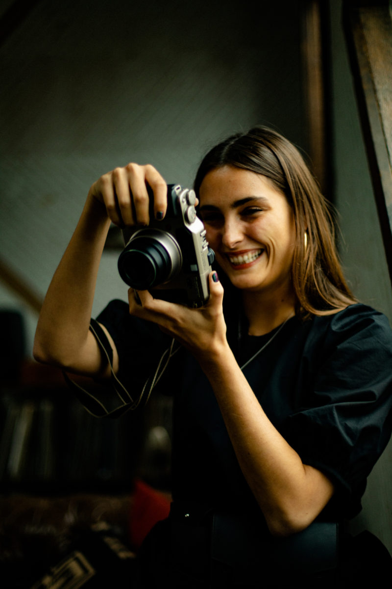 a brunette woman wearing black holds a film camera in front of her face