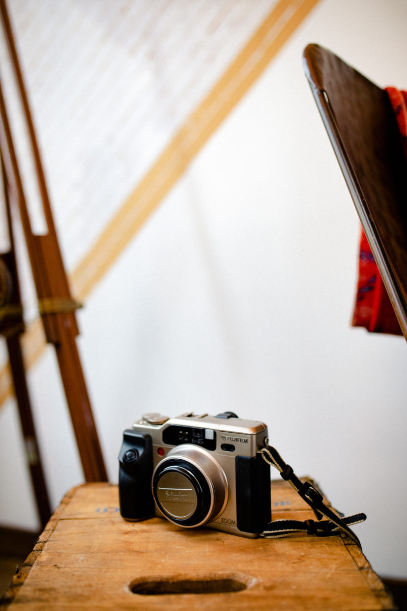 a film camera sits on a wooden table