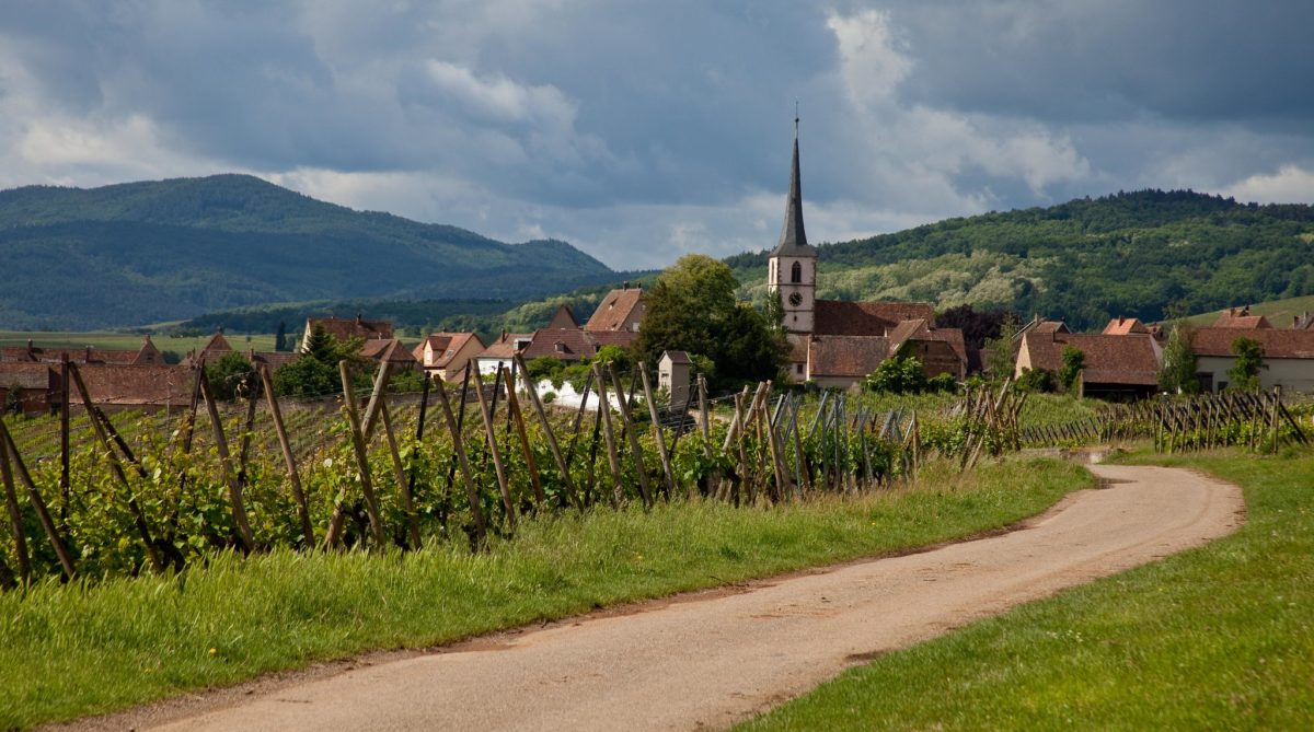 a path leads to a village in the middle of green mountains in the center of which sits a church with a thin gray spire