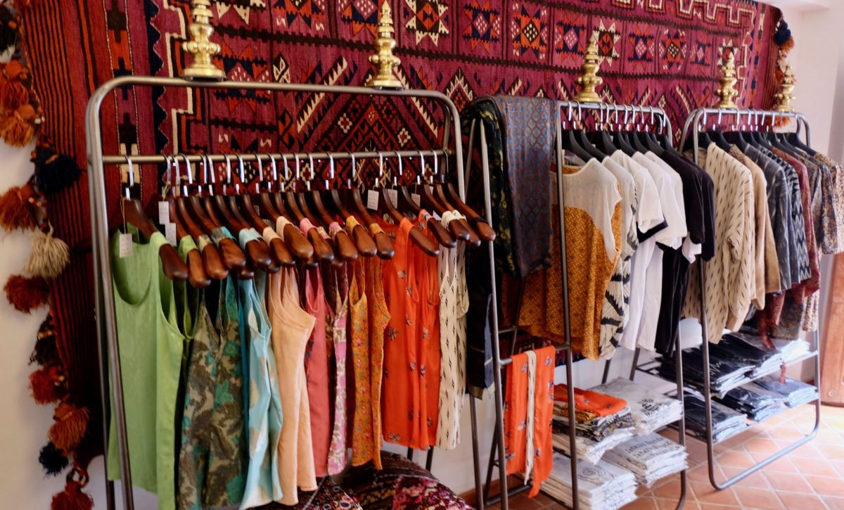 a rack of colorful shirts at Of Silk and Salt's boutique