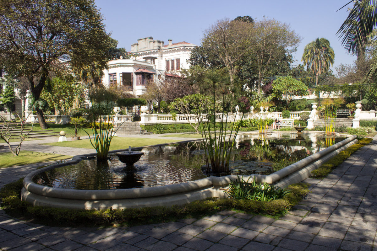 a pond and mansion in sunny garden of dreams in kathmandu nepal.