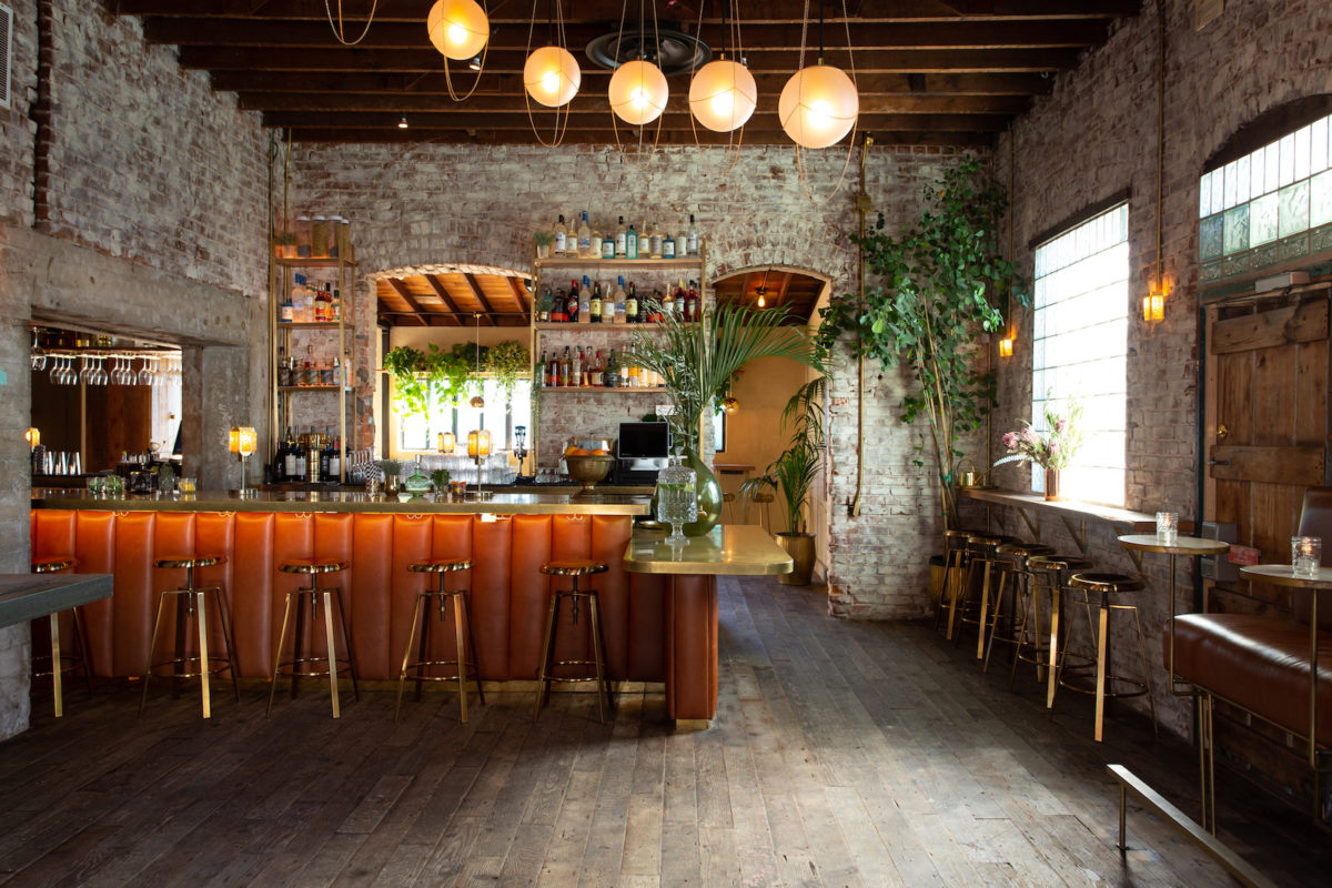 a beach-rustic restaurant with light gray floors, plants, and large orange light fixtures