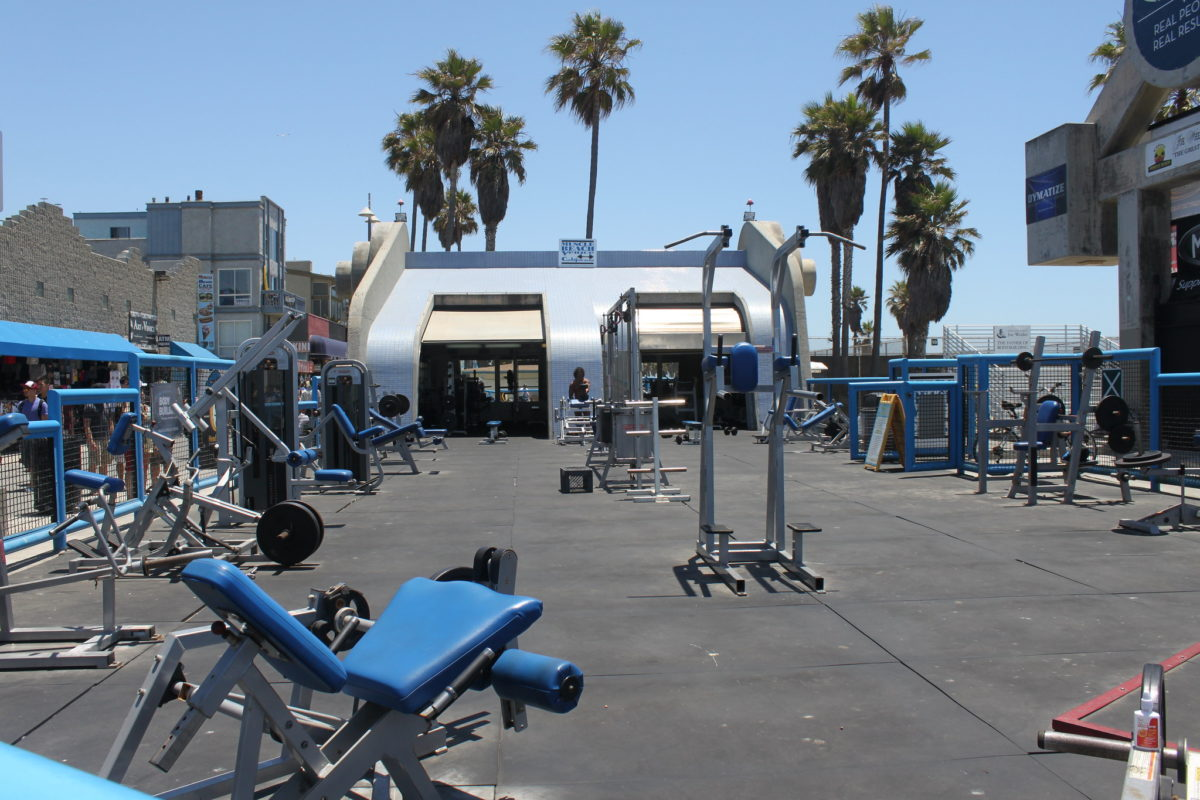 a blue trailer sits at the back of a concrete lot filled with exercise equipment with palm trees in the background