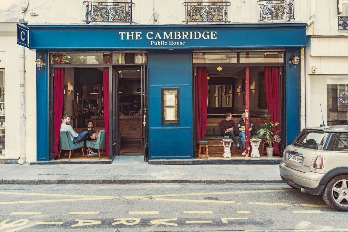 "the facade of a pub called ""The Cambridge"" with a deep turquoise exterior and red curtains"